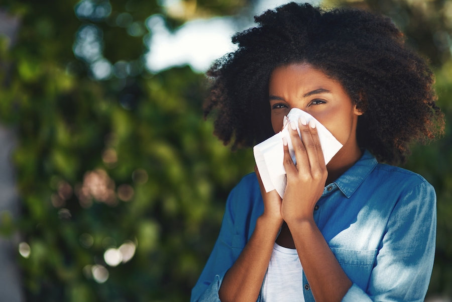 Beautiful woman blowing her nose because it is allergy season in Marble Falls, Texas, and she is wondering if her air conditioner can help with her allergies.