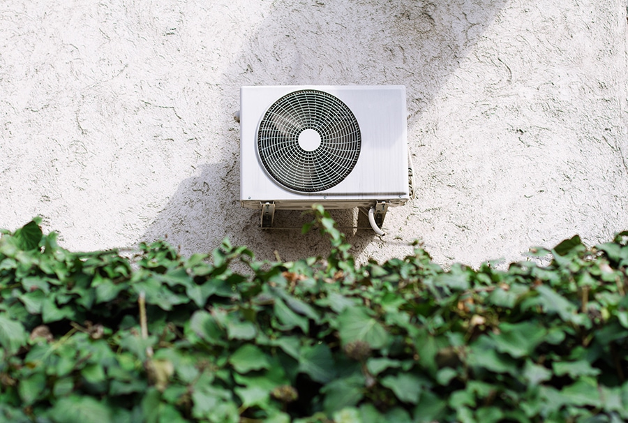 Horizontal front view of a white central air conditioner behind a decorative garden wall of green leaves.