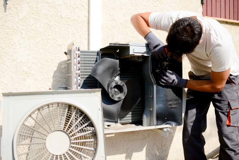 young man electrician installer working on a split-system air conditioning unit at a client's home in Marble Falls, TX